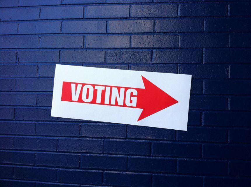 Voting sign on brick wall
