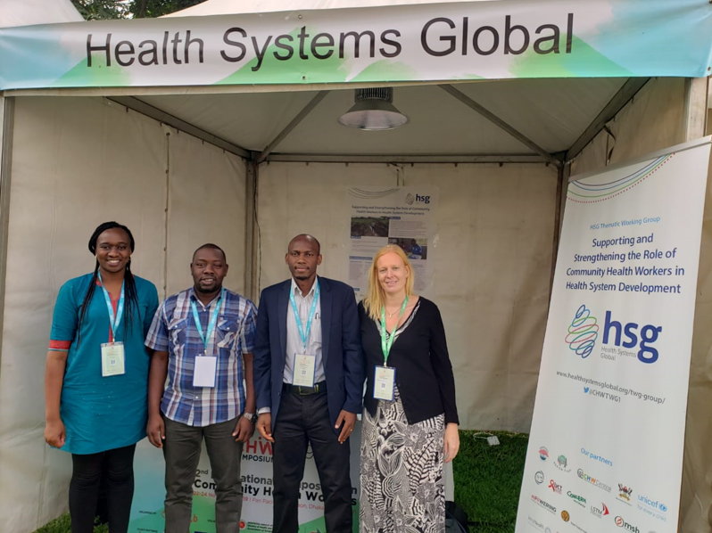 Leads of the HSG Community Health Workers Thematic Working Group stand in front of an HSG booth at the CHW Symposium