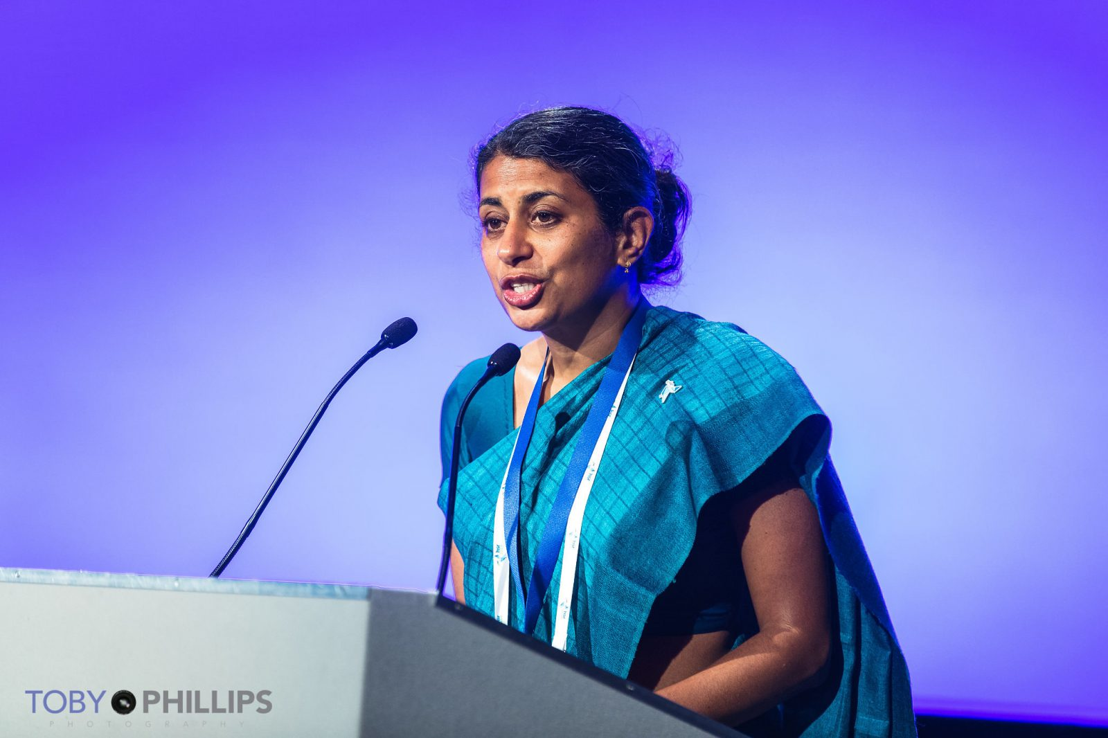 Asha George standing at a podium reading the HSR2018 Liverpool Statement