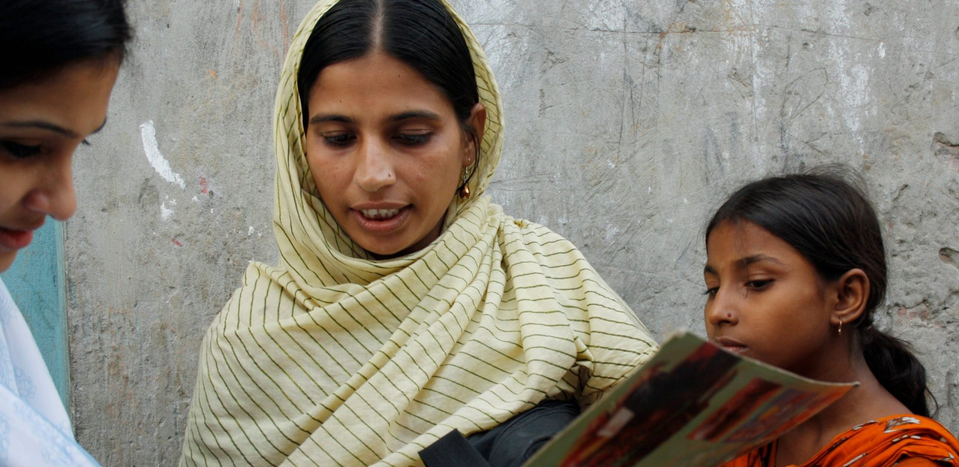 A community health working in India speaking to a woman and her daughter