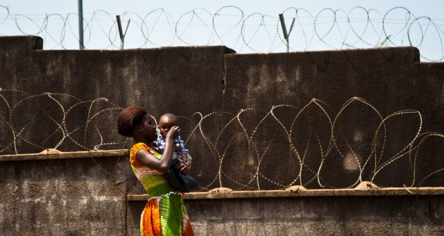 Woman carrying baby walking past barbed wire on top of a wall