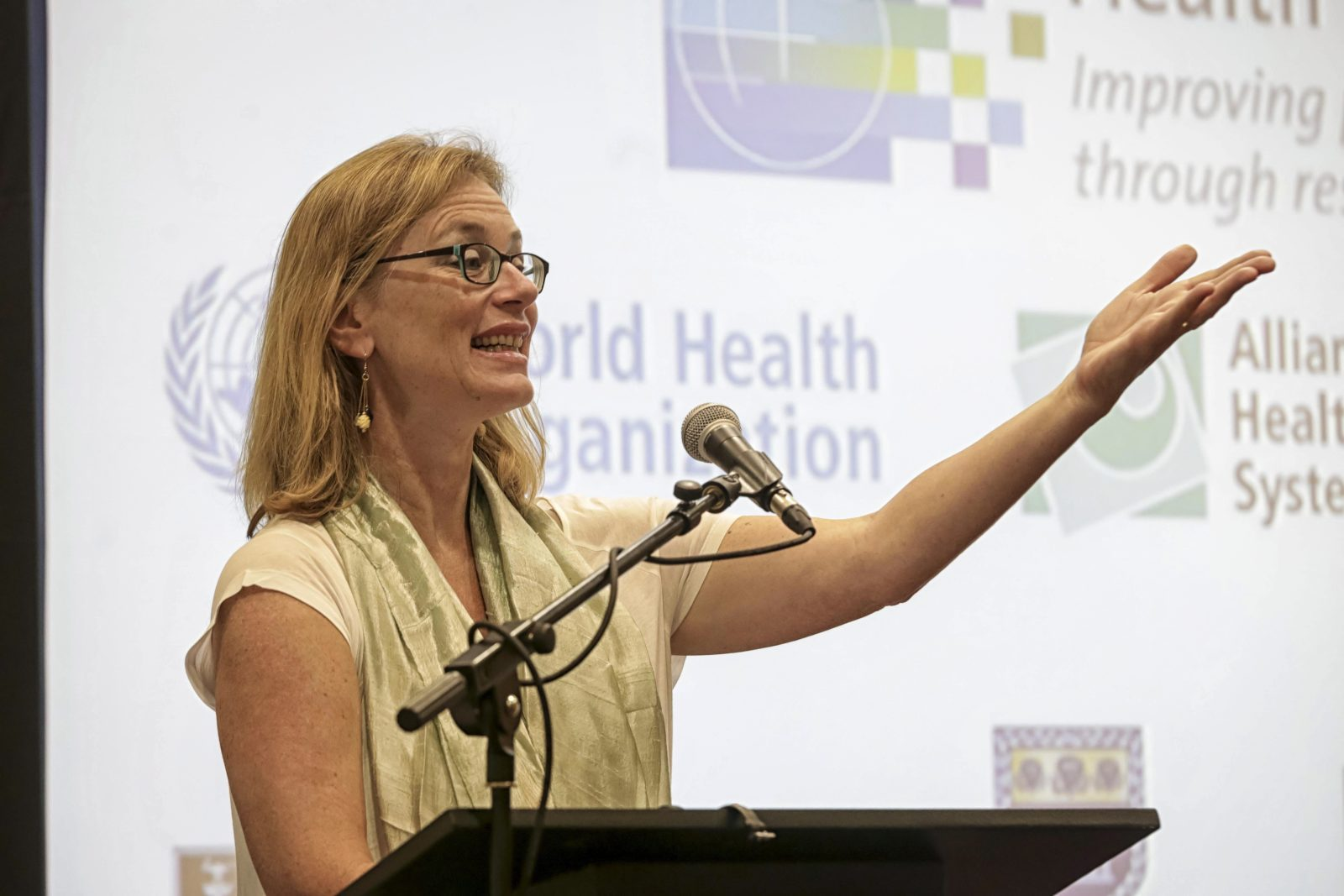 Sara Bennett standing at a podium and speaking at HSR2014