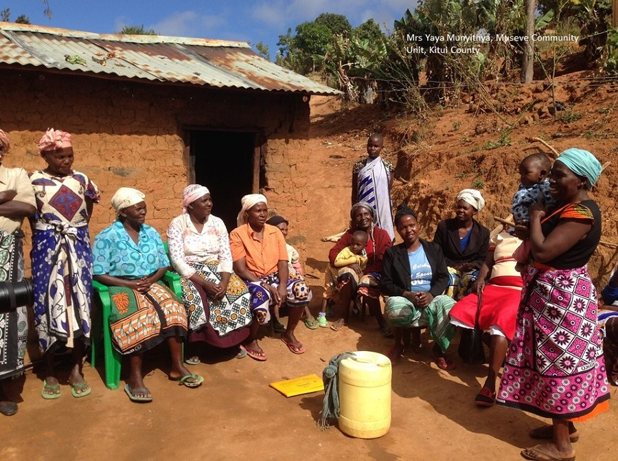 Community health worker speaking to women outside a mud house