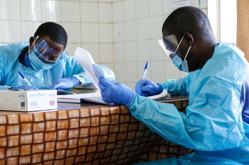 Two doctors in PPE looking at patient records