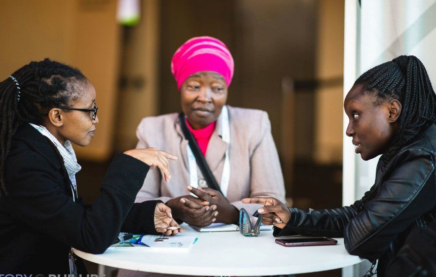 Three female professionals engaged in discussions