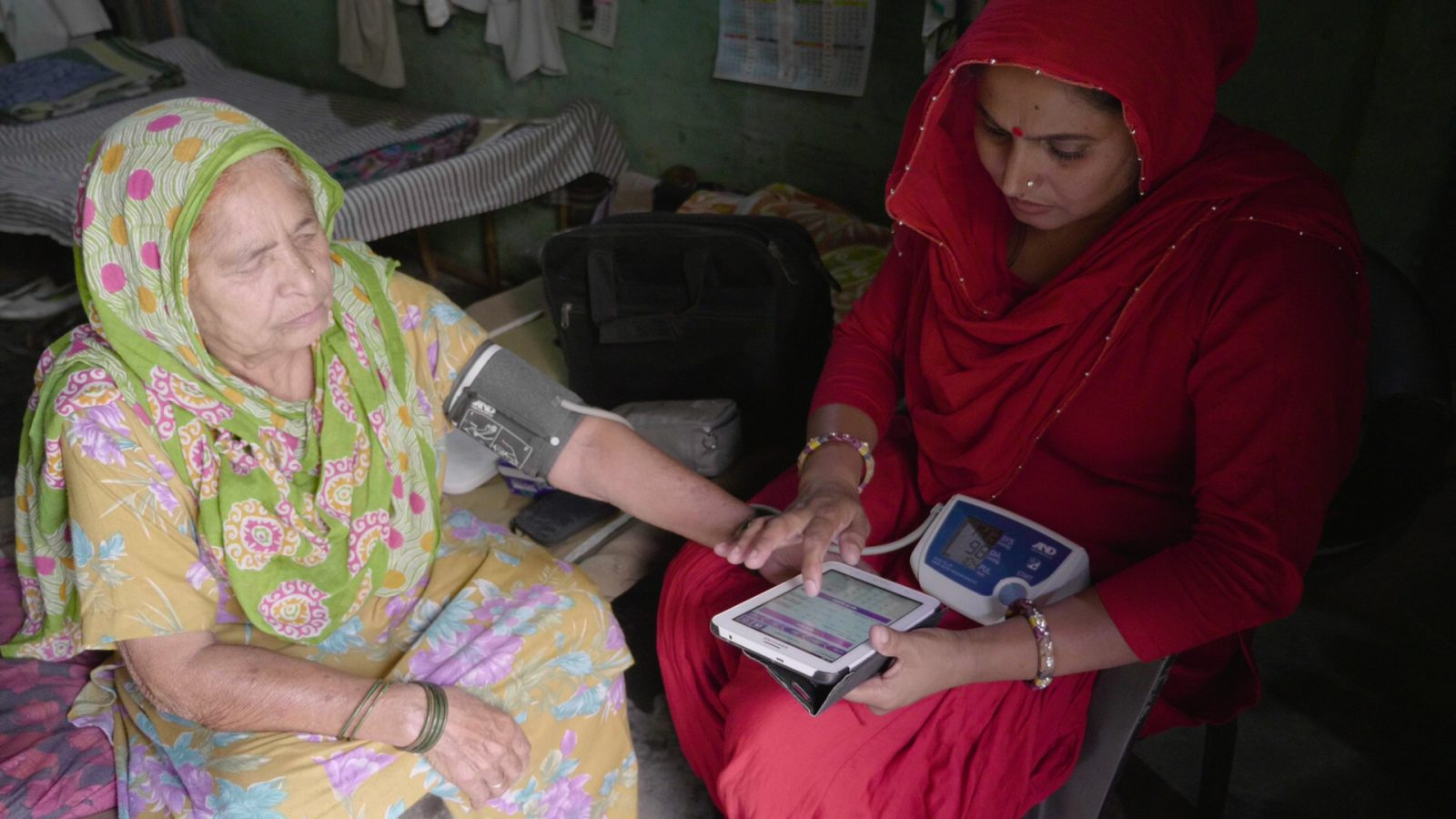 Woman getting her blood pressure taken by a Community Health Worker in Delhi, India