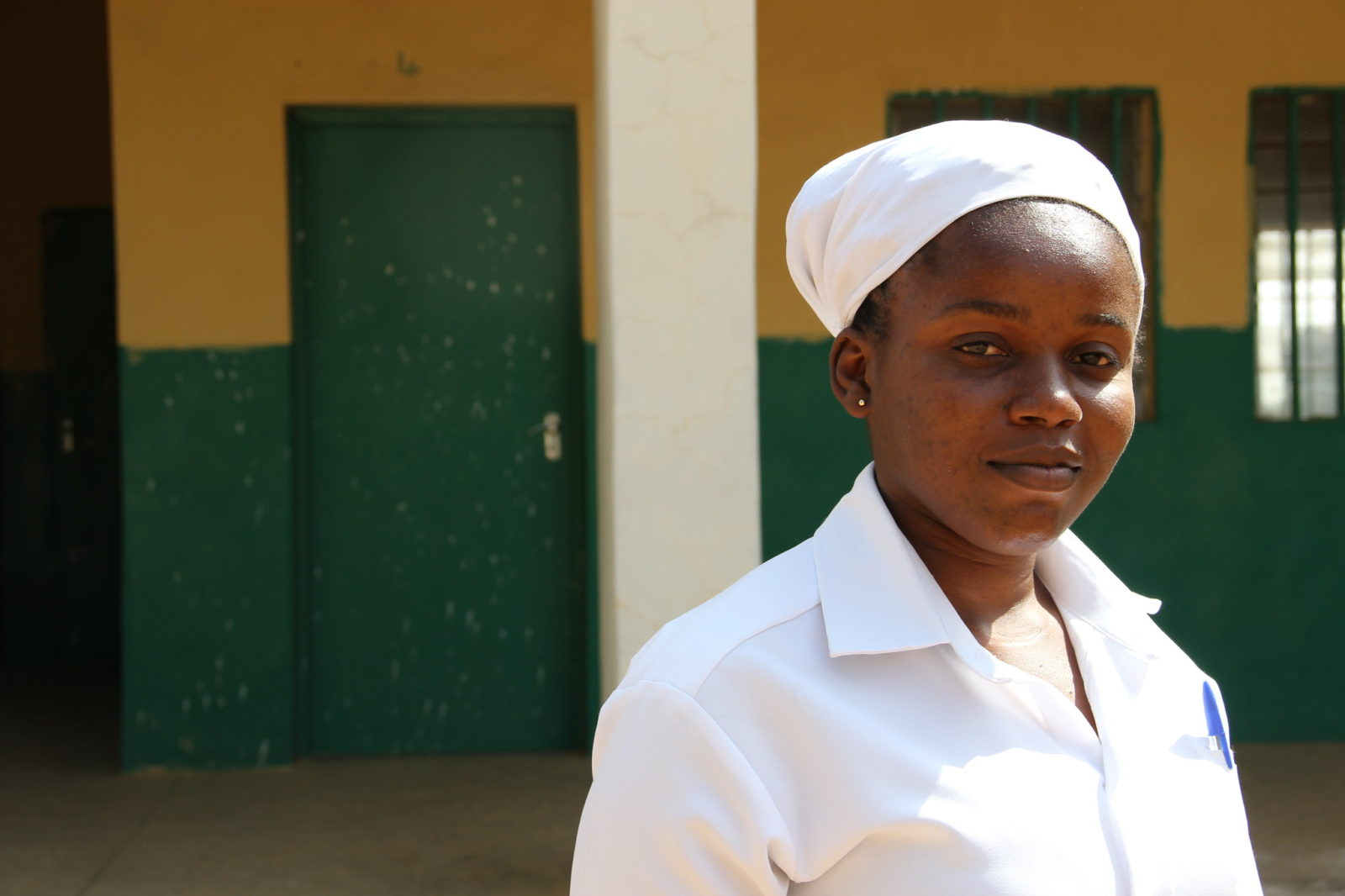 Midwife standing in front of a health facility in Northern Nigeria