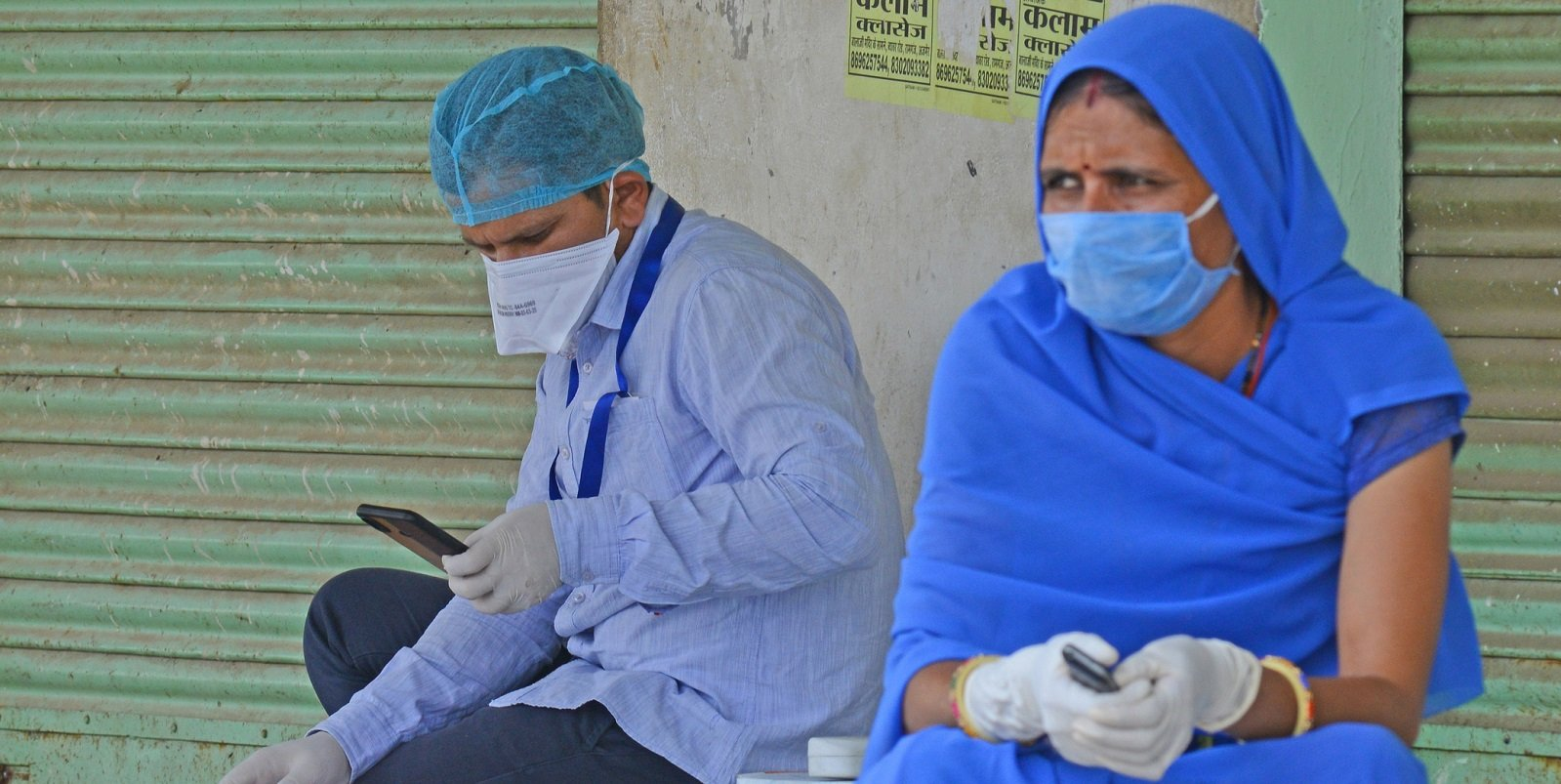 A male and female community health worker sitting down. The male health worker is looking at his mobile phone.