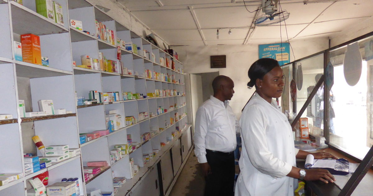 Two pharmacists standing belhind the counter at a pharmacy, with medicines lining the shelves behind them.