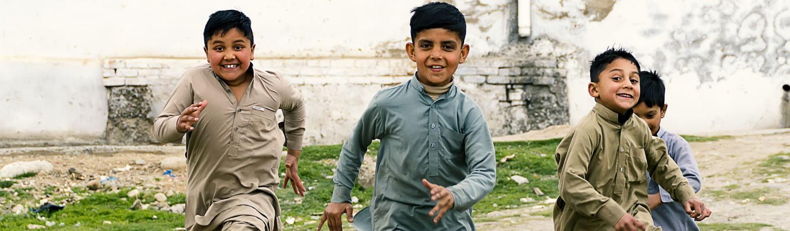 Four boys in Pakistan playing and running towards the camera