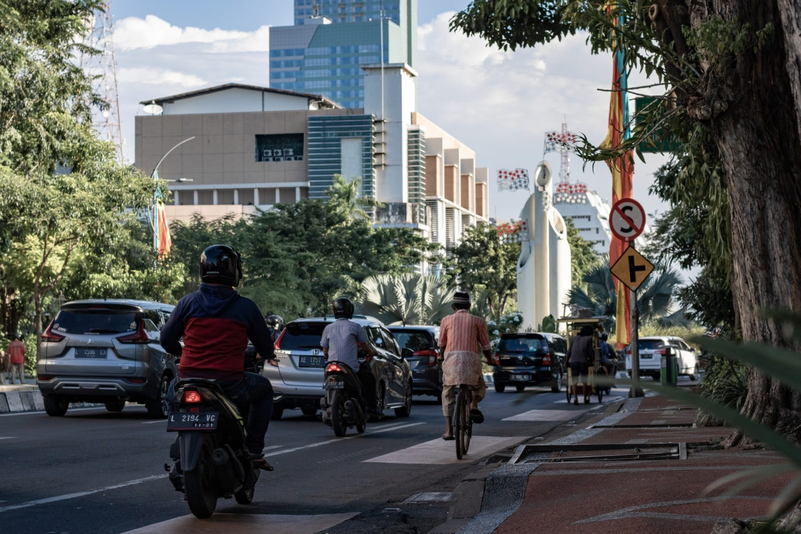 Street scene in Indonesia. A road with cars and scooters and cyclist