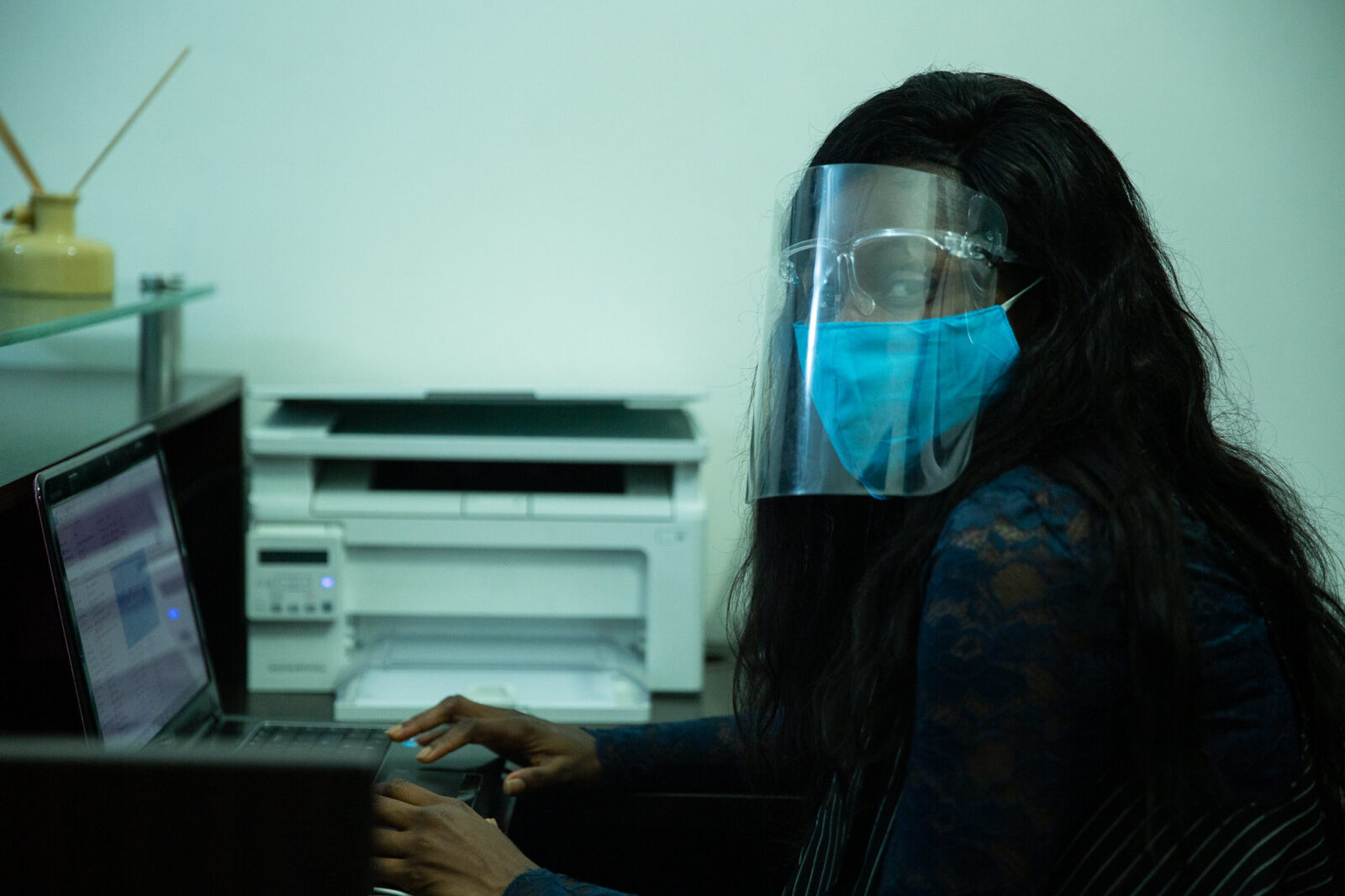 Adenike Onatoye, an Administrative head, works in the office with her face mask and face shield on.